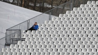 A spectator sits in an empty tribune at the downhill run of the women's alpine skiing super combined event during the 2014 Sochi Winter Olympics