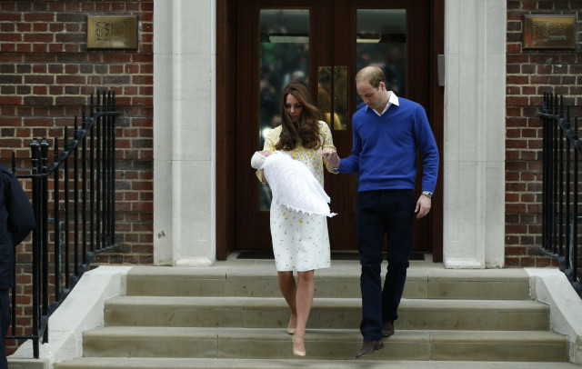 Britain's Prince William, right, helps Kate, Duchess of Cambridge, walk down the steps as they pose for the media with their newborn daughter outside St. Mary's Hospital's exclusive Lindo Wing, London, Saturday, May 2, 2015. The Duchess gave birth to the Princess on Saturday morning. (AP Photo/Alastair Grant)