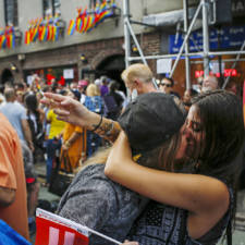 Women kiss each other as people celebrate outside the Stonewall Inn in the Greenwich Village neighborhood of New York