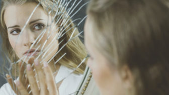 Woman touching broken mirror