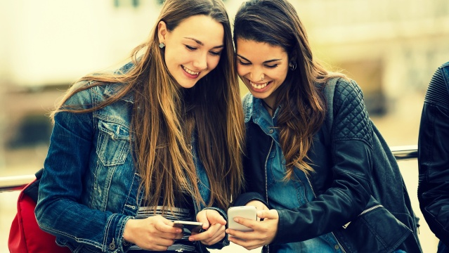 Portrait of two beautiful students using mobile phone in the street.