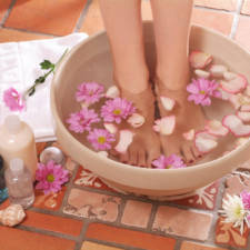 Feet stood in bowl of water with flowers next to lotions