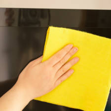 Young woman cleaning a tv flat