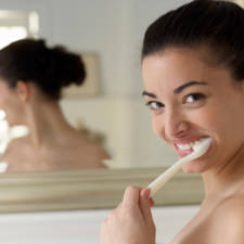 Young woman brushing teeth, close up, portrait