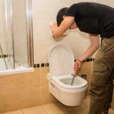 Young man cleaning the bathroom lavatory, wiping latrine