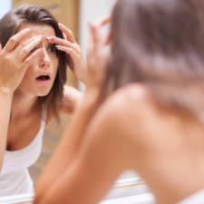 Shocked woman squeezing pimple in bathroom