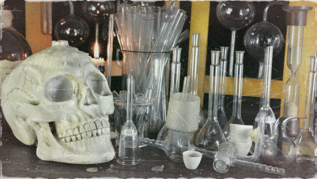 Human skull with bottles on witch table in alchemy laboratory