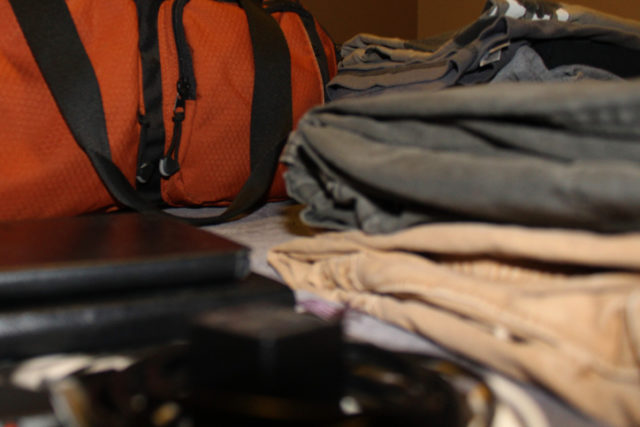 Neatly Folded Clothes in front of Orange Duffle Bag