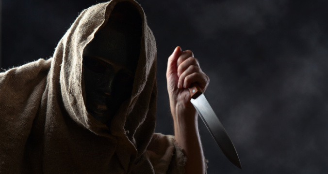 Hooded man in mask with a knife