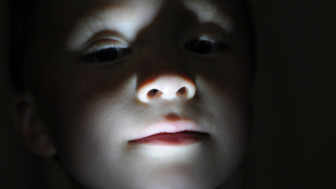 Little boy portrait in the dark making horror