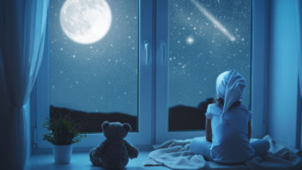 Child little girl at window dreaming and admiring starry sky