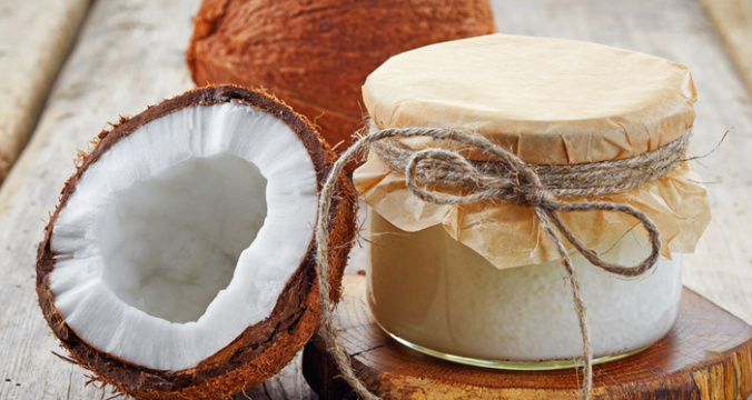 A coconut jar with coconut oil and coconuts sliced in half