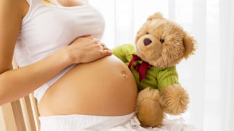 Pregnant woman holding teddy bear to her tummy