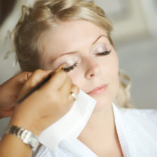Beautiful, cute blond bride doing makeup before wedding day.