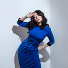 Beautiful young brunette woman in blue dress against
