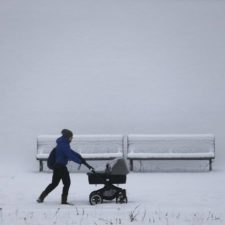 18 parent pushes a pushchair along a snow covered bank.jpg