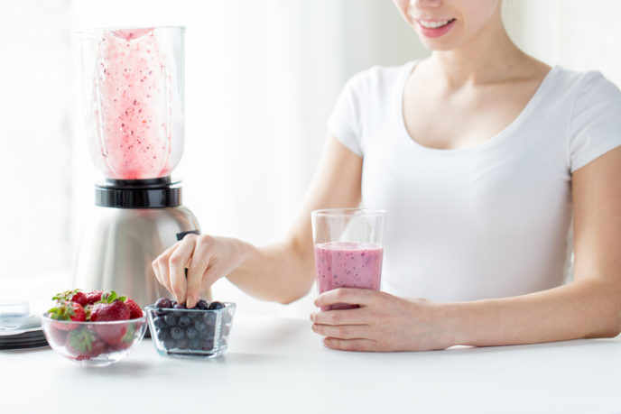 Close up of woman with blender and milk shake