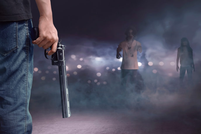 Brave man with jeans pants holding gun looking at zombies