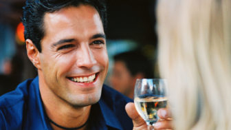 Close up of a man holding a glass of wine and smiling at a woman