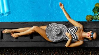 Woman Summer Fashion. Sexy Girl Sunbathing By Swimming Pool. Beaty