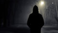 Silhouette of hooded person with spooky dark background