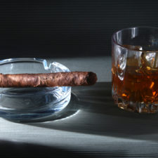 Glass of whiskey or bourbon with ice and cigar on black stone table. Selective focus.