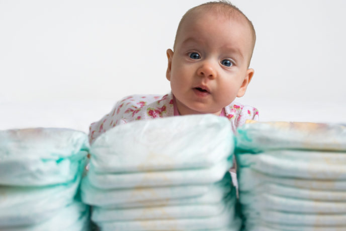 Baby looking over stack of diapers 1 v 2