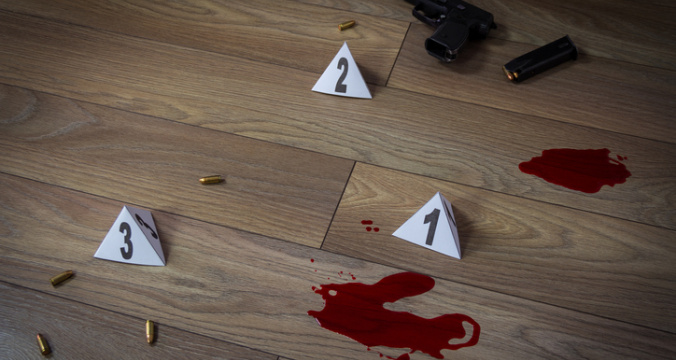 Crime scene indoors with traces of blood, handgun pistol and bullets