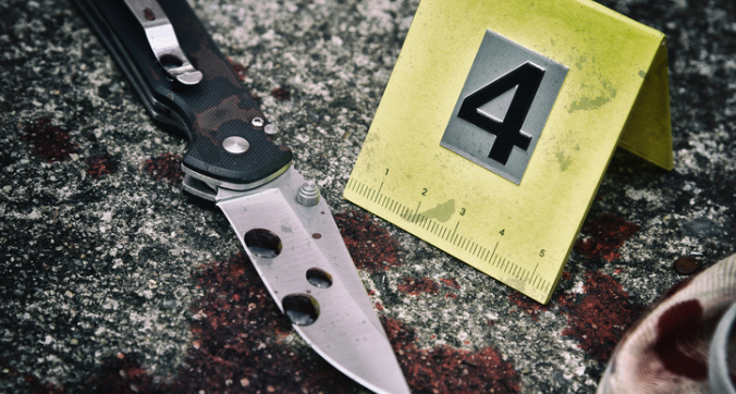 Crime scene investigation, Bloody knife and victim's shoes with criminal markers on ground