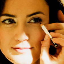 Close up of a mid adult woman applying eye liner