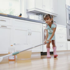 Girl (6 8) cleaning kitchen floor with mop, smiling, low angle view
