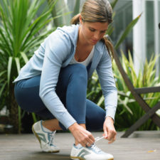 Woman kneeling on decking tying laces of running shoes