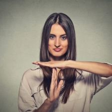 Young, happy, smiling woman showing time out gesture