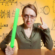 Mean female teacher holding ruler and pointing her finger