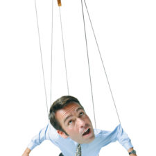 conceptual caricature of a caucasian business man in a shirt and tie as he hangs in the air by strings as a marionette puppet