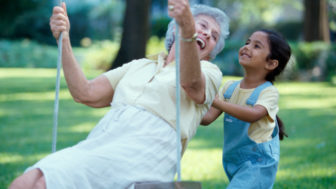 Side profile of a granddaughter pushing her grandmother on a swing