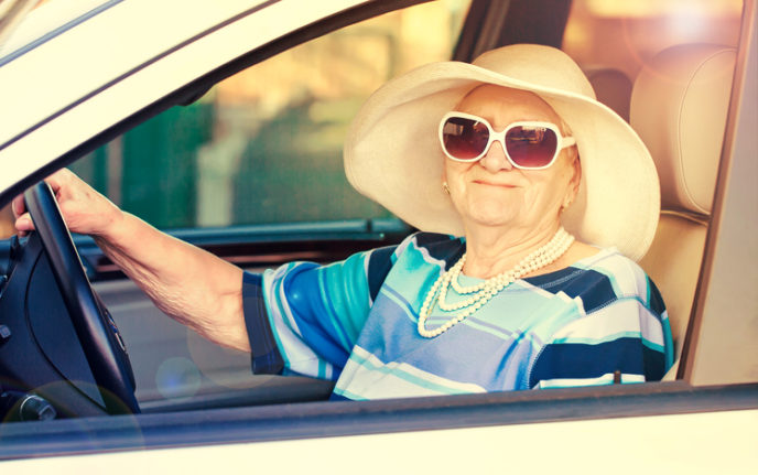 Happy senior woman in sunglasses and hat driving automobile