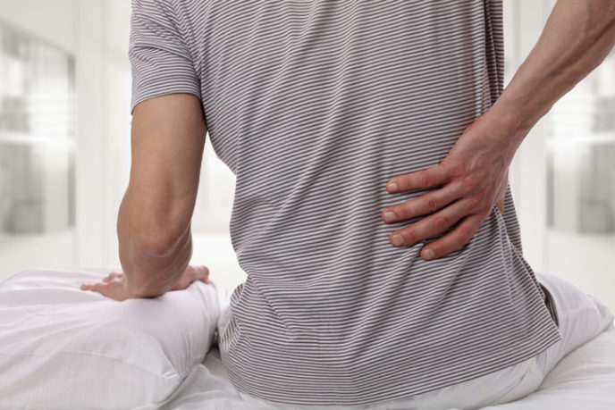 Man suffering from back pain at home in the bedroom. Uncomfortable mattress and pillow causes back pain.