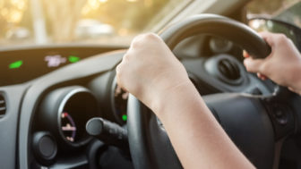 Woman's hands on car steering wheel