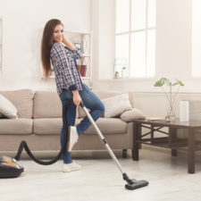 Happy woman cleaning home with vacuum cleaner