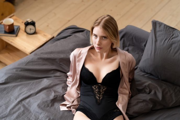 Young gorgeous female in black lingerie and beige silk pajamas looking at you