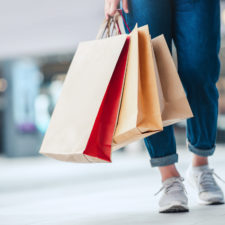 Woman holding sale shopping bags. Consumerism, shopping, lifestyle concept