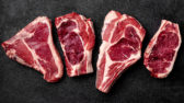 Meat raw steak lies on a black background. side view, copy space, top view