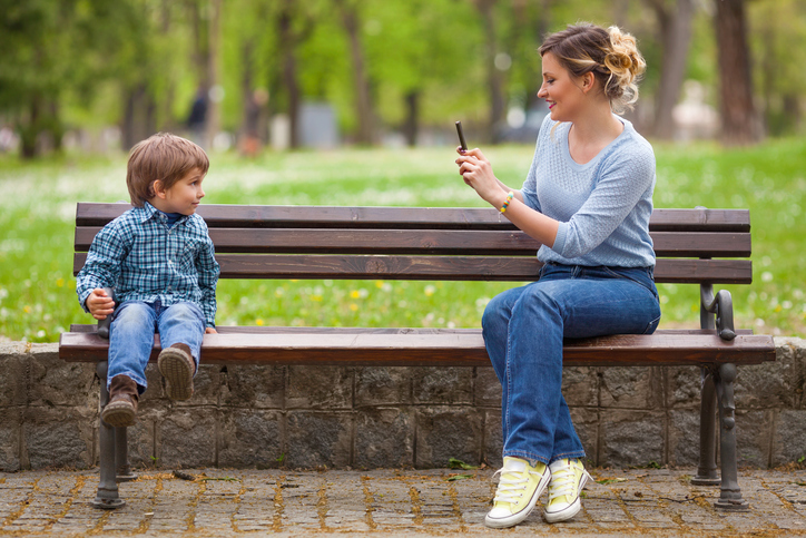 Young mother photographing her cute little son sitting on a park bench