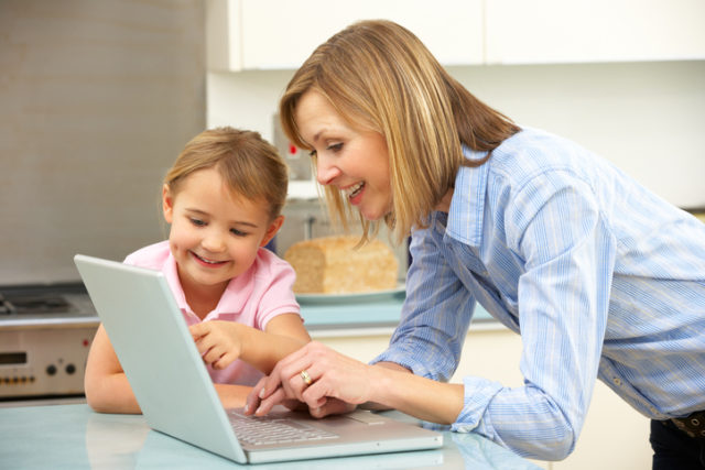 Mother and daughter using laptop in domestic kitchen at table chatting