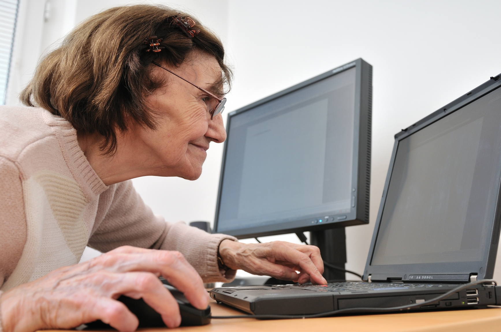 80-something senior woman working with laptop, another computer in the background