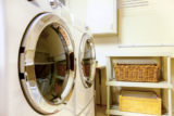 Old style laundry room with modern appliances and wicker baskets