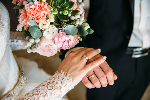 Groom and bride are holding hands at wedding day