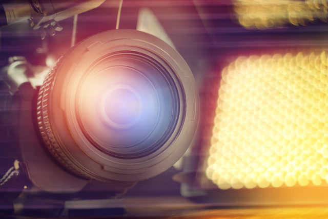Professional video camcorder in studio with blurred spot light background