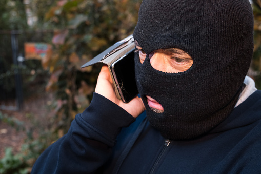 Masked thief talking on his mobile phone. Outdoors